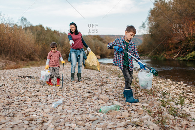 Two brothers with garbage pickers cleaning up plastic bottles in the nature. Children walking along river beach picking up plastic waste with their mother.