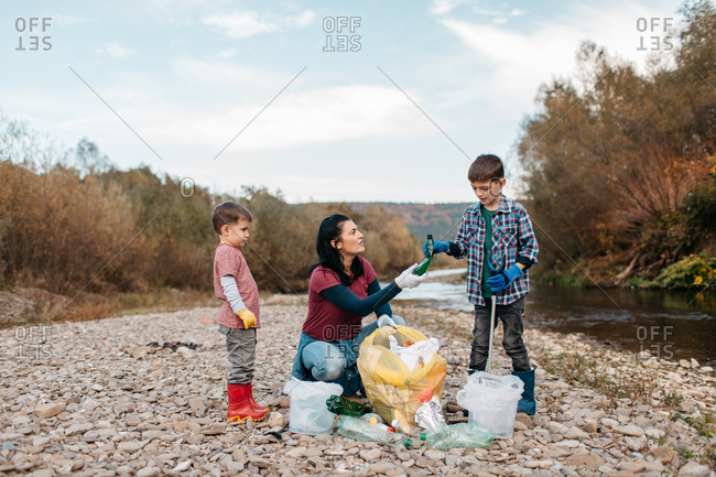 Two boys wearing gloves and boots collecting trash into bags and buckets in the nature. Children sorting out plastic waste at river beach with their mother.