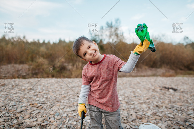 Young boy wearing rubber gloves making faces whilst collecting garbage in the nature. Portrait of child holding green plastic bottle and waste picker.