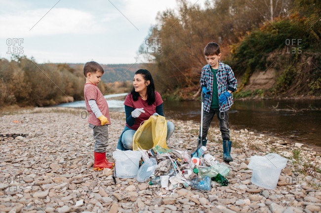 Two boys and their mother wearing gloves and boots collecting trash into bags and buckets in the nature. Female volunteer teaching children about sorting out waste at river beach.
