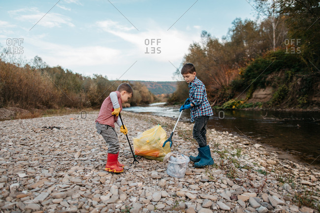 Two kids with trash pickers cleaning garbage on the beach on autumn day. Cleanup - children volunteers picking up plastic waste from river beach.