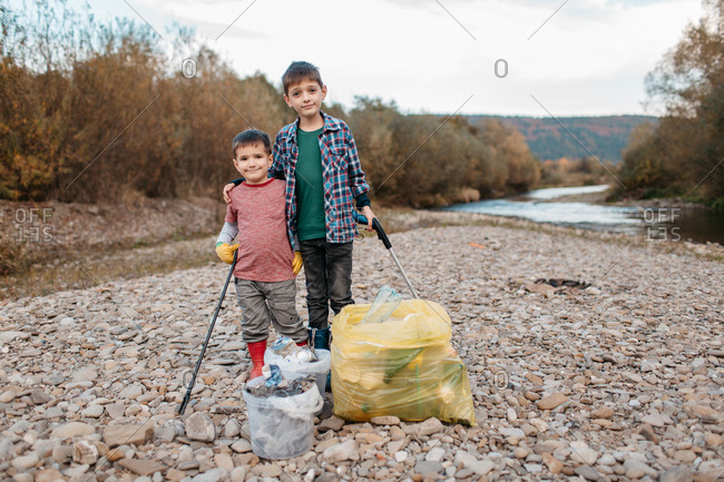 Front view of two young boys with trash pickers embracing after cleaning up river beach. Portrait of children volunteers standing at plastic bags and buckets filled with rubbish.