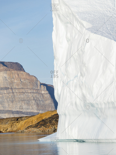 Landscape with steep yellow cliffs and icebergs in the Uummannaq fjord system, northwest Greenland.