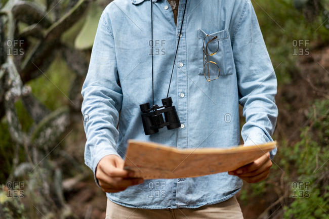 Young man standing in nature- looking at map