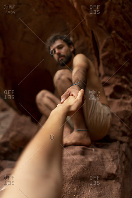 Young man sitting in a cave- reaching out for woman's hand