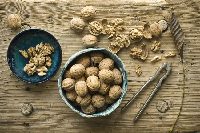 Whole and cracked walnuts in bowls on wood