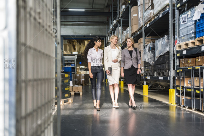 Three women with tablet walking and talking in factory storehouse