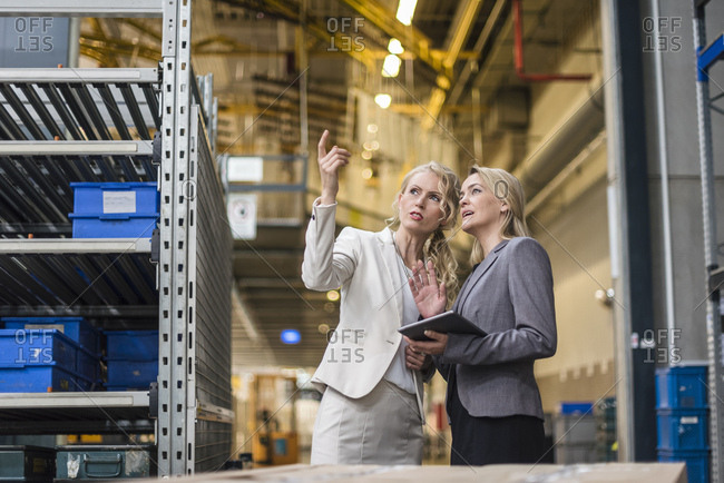 Two women with tablet talking in factory storehouse