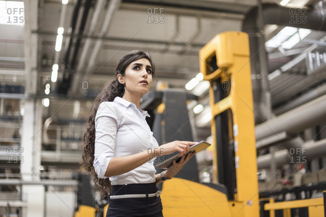 Woman with tablet in factory shop floor looking around