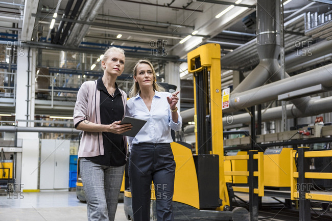 Two women with tablet walking and talking in factory shop floor