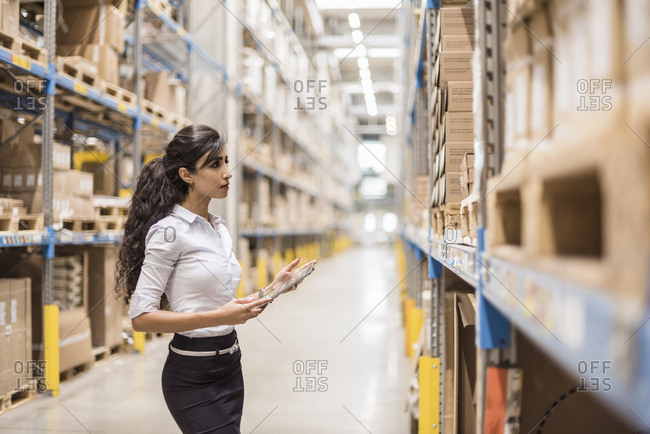 Woman with tablet in factory storehouse looking at shelf