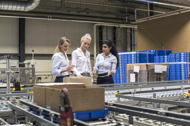 Three women discussing at conveyor belt in factory