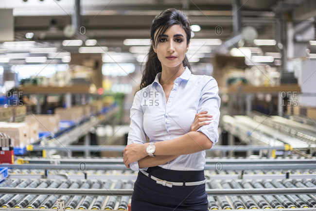 Portrait of confident woman at conveyor belt in factory