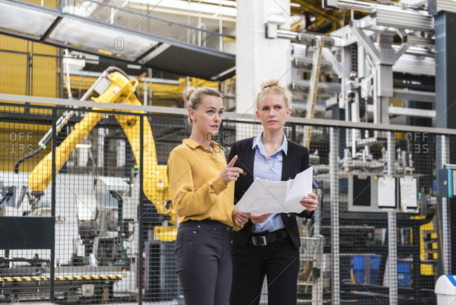 Two women discussing plan in factory shop floor with industrial robot