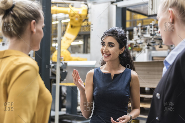 Portrait of smiling woman talking to colleagues in modern factory