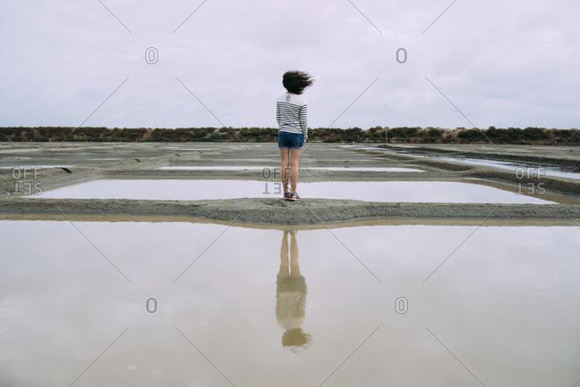 France- Bretagne- Woman surrounded by salt ponds in Marais salants de Guerande