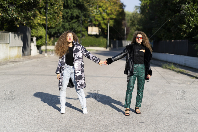 Portrait of fashionable twin sisters holding hands