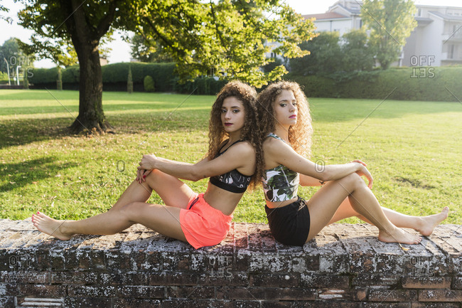 Portrait of twin sisters sitting barefoot back to back on a wall in summer