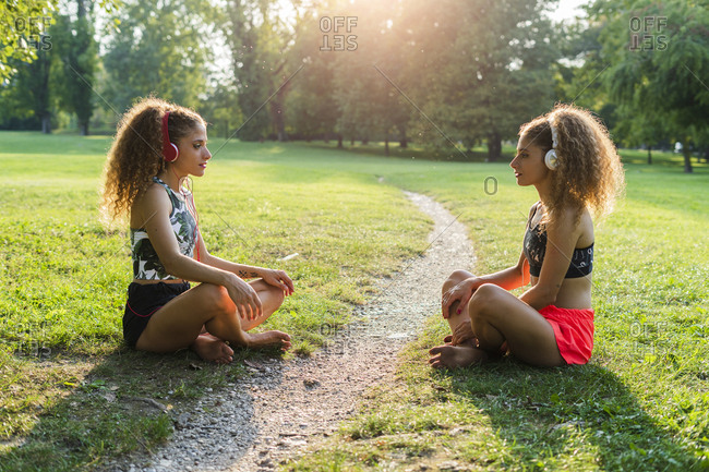 Twin sisters sitting on a meadow in a park listening music with headphones