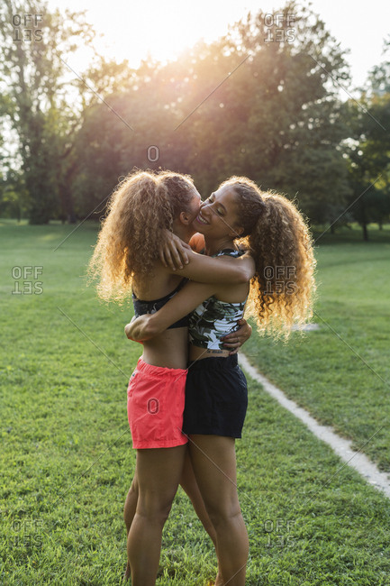 Twin sisters hugging each other in a park