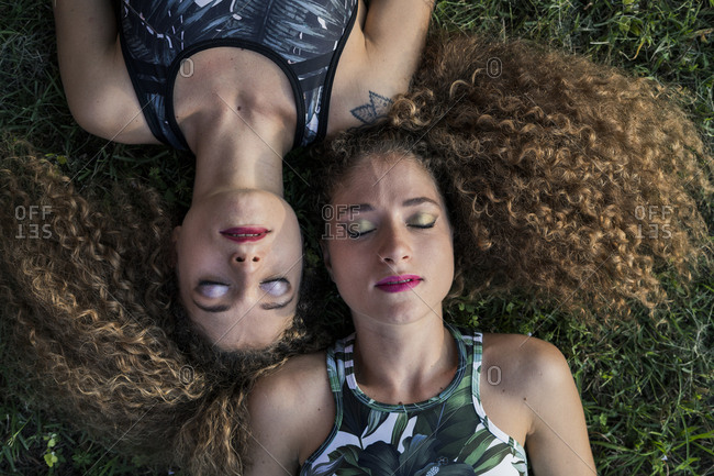 Portrait of rouged twin sisters lying on a meadow- top view