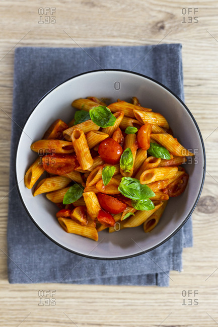 Penne with tomato and basil in bowl from above