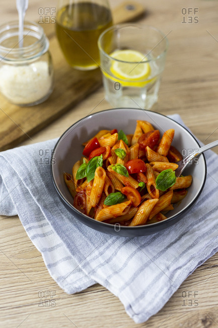 Penne with tomato and basil in bowl