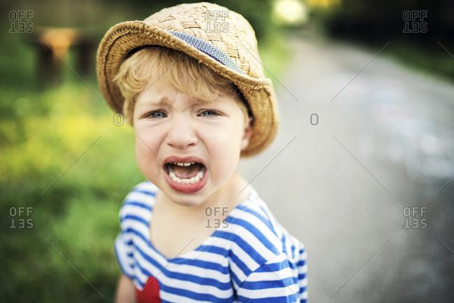 Portrait of screaming toddler wearing straw hat