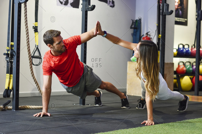 Couple exercising side plank with high-five in a gym