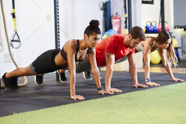 Young people exercising plank variations in a gym