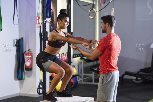 Trainer assisting client- doing box jumps