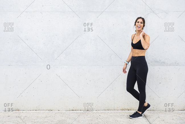 Laughing athlete standing in front of white wall