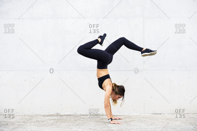 Athlete doing handstand in front of white wall