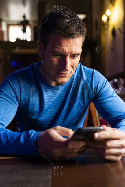 Man wearing sports jersey using cell phone at table