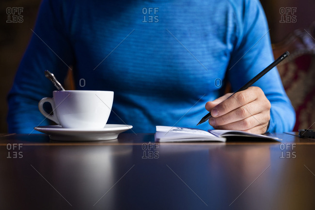 Close-up of man drawing into sketchbook at table