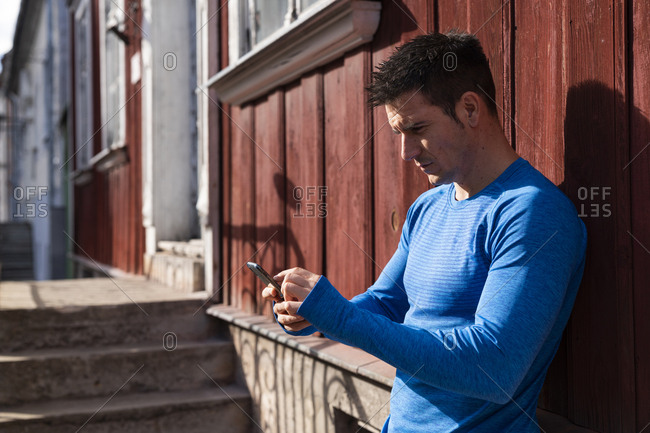 Athlete leaning against house wall using cell phone