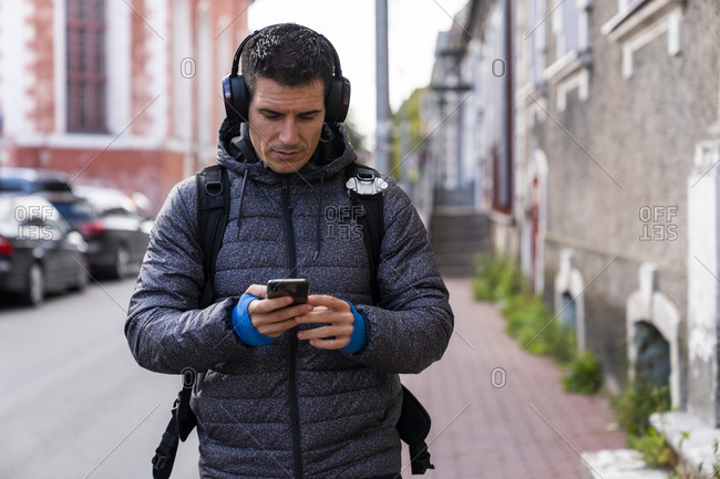 Man in the city on the go with cell phone and headphones