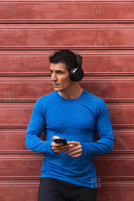 Athlete leaning against house wall holding cell phone