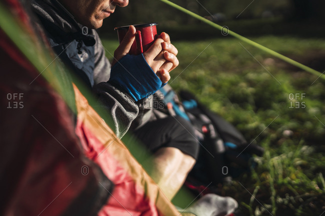 Man camping in Estonia- sitting in tent- drinking coffee