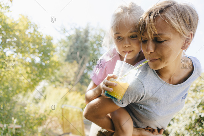 Mother carrying daughter piggyback in garden drinking a smoothie
