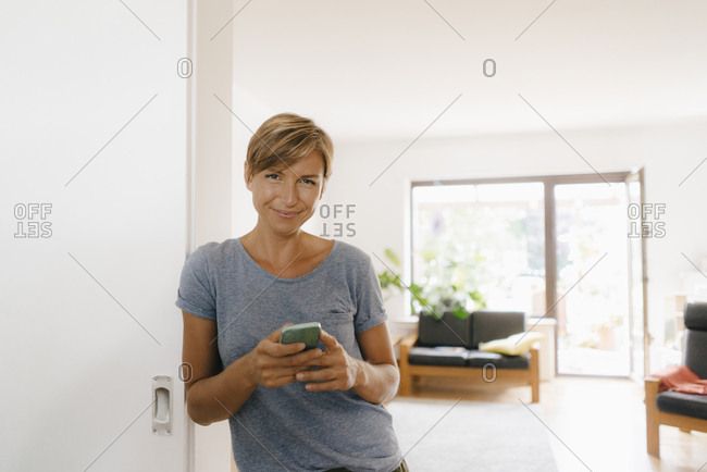 Portrait of smiling woman at home holding cell phone