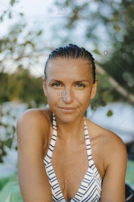 Portrait of smiling woman with wet hair wearing a bikini at a lake