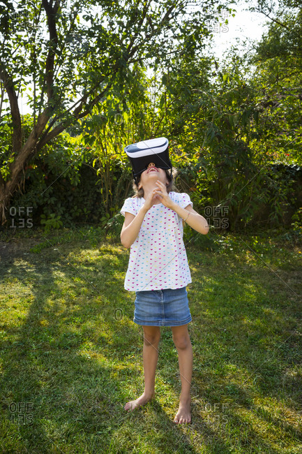 Little girl wearing Virtual Reality Glasses in the garden