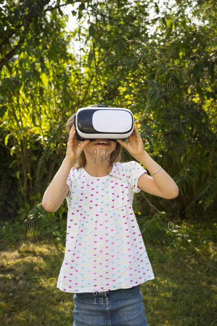 Amazed little girl wearing Virtual Reality Glasses in the garden