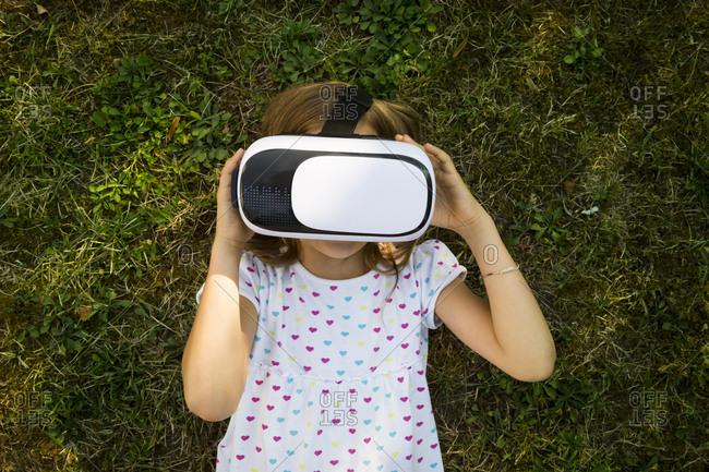 Little girl wearing Virtual Reality Glasses lying on meadow in the garden