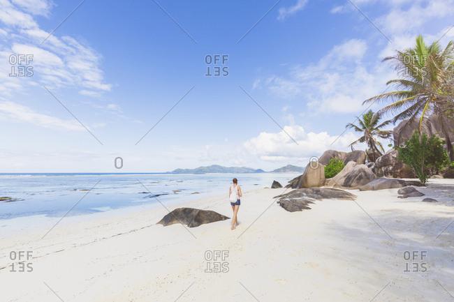 Seychelles- La Digue- Anse Source d'Argent- woman walking at the beach