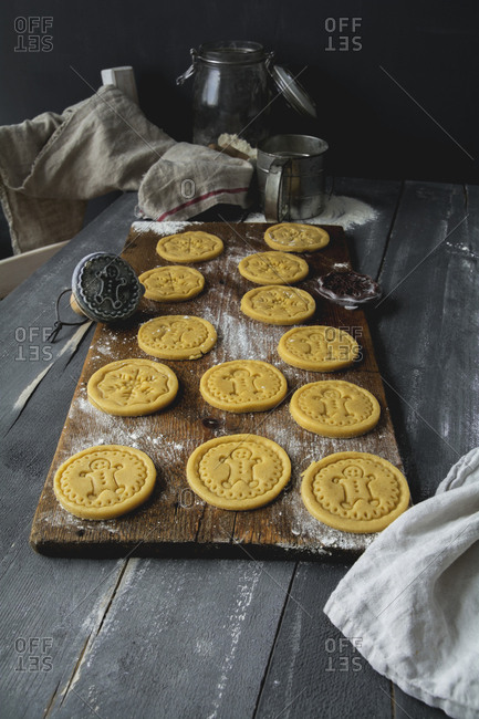 Raw short crust motif cookies and cookie stamp on wooden board