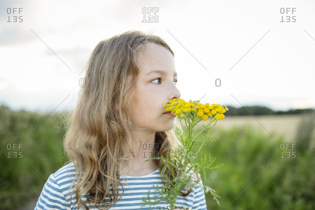 Girl in nature smelling at a wild flower