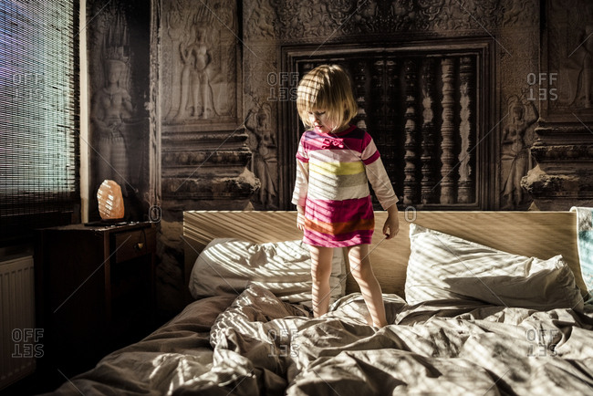 Little girl standing on parent's bed at home