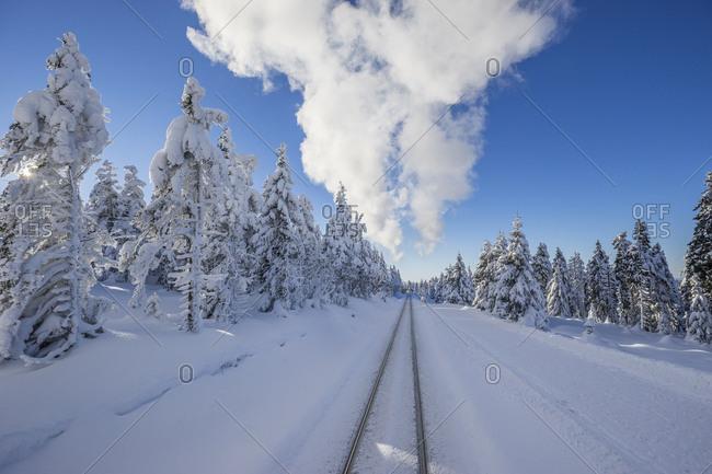 Germany- Saxony-Anhalt- Harz National Park- Brocken- rail tracks of Harz Narrow Gauge Railway in winter- cloud of steam
